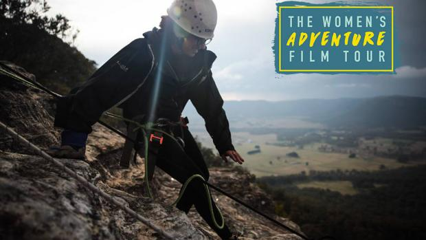 Image of girl abseiling down a mountain with a Women's Adventure Film tour logo