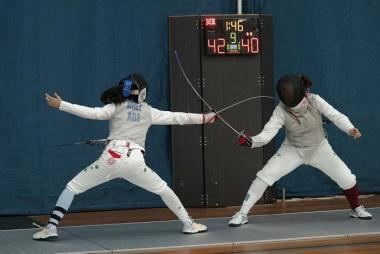 Two girls compete in a fencing contest in a tournament