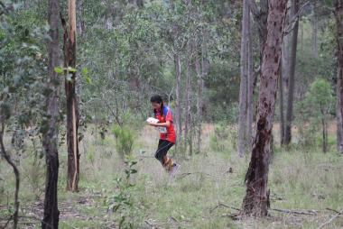 Girl reading map in woods as part of orienteering course