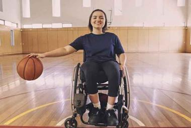 Girl in wheelchair playing basketball