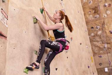 Girl climbing an indoor rock climbing wall