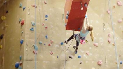 Girl climbing and indoor rock climbing wall